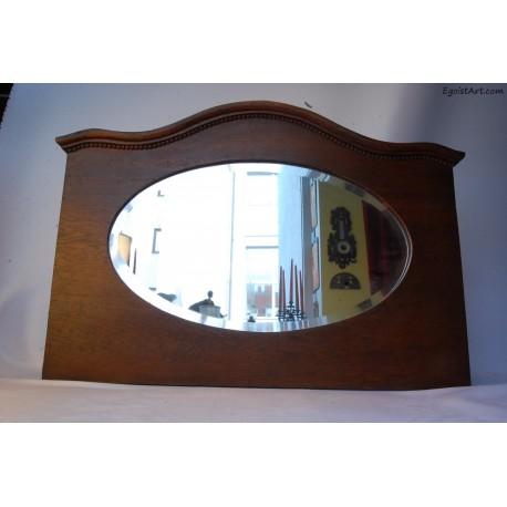 Owalne lustro w drewnianej zabudowie